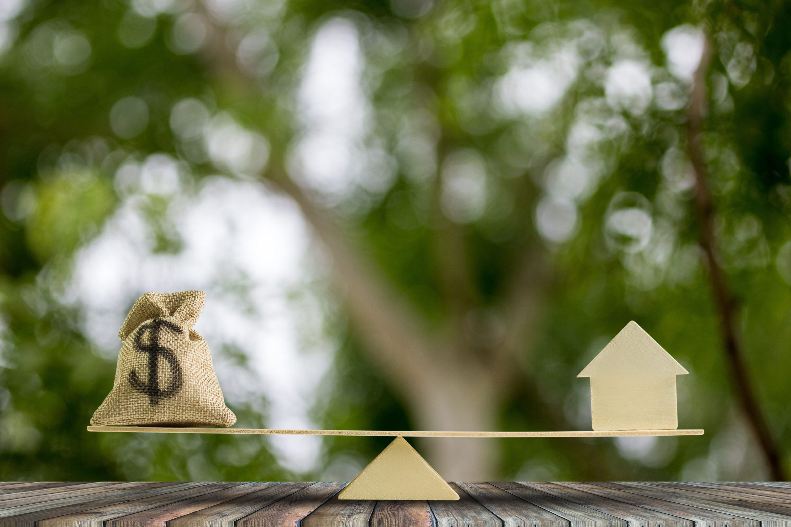 Money and home,loan,mortgage. Change home into cash concept : US Dollar in sack bag, Wooden house model put on scales on wood table with green tree bokeh as background. Balance home and debt.